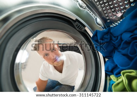 Portrait Of Young Man View From Inside The Washing Machine With Clothes