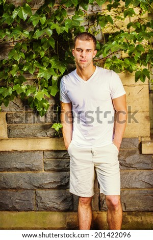 Portrait of young man. Wearing a white V neck T shirt, light yellow shorts, a young guy is standing against a wall with green ivy leaves, confidently looking at you.  - stock photo