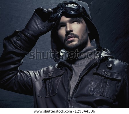 Portrait of young man wearing aviator headgear - stock photo