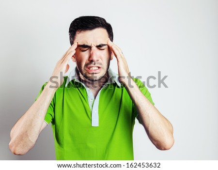 Portrait of young man wearing green shirt having head pain.Grey background.