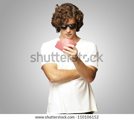 portrait of young man wearing sunglasses and playing poker over - stock photo