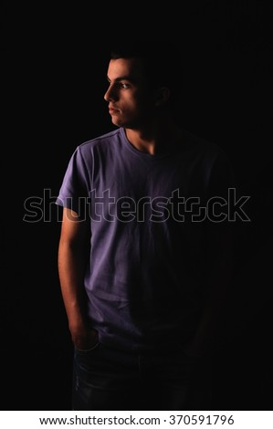 Portrait of young man wearing t-shirt standing with hands in pockets and looking on one side isolated on black background - stock photo