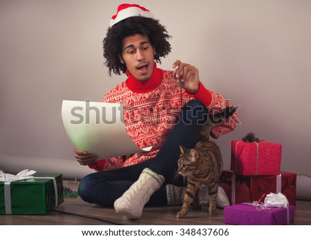 Portrait of young man with afro sitting at his room and preparing Christmas letter or wish list - stock photo