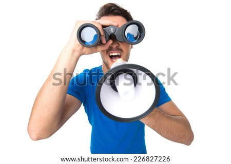 portrait of young man with binoculars and loud speaker over white background. top view of young man looking through binoculars up - stock photo