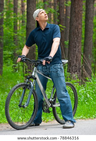 Portrait of young man with cycle in park - stock photo