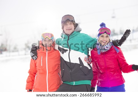 Portrait of young man with female friends enjoying in snow - stock photo