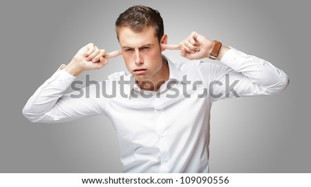 Portrait Of Young Man With Finger In His Ear On Gray Background - stock photo