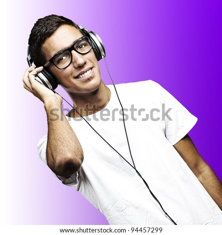 portrait of young man with glasses and headphones listening to music on a purple background - stock photo