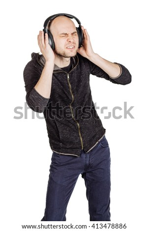 portrait of young man with headphones listening music and dancing . image isolated white background - stock photo