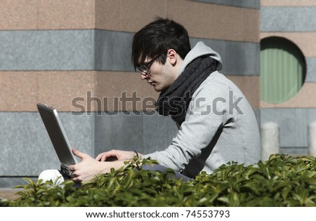 portrait of young man with his laptop, outdoors - stock photo