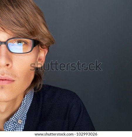 Portrait of young man with smart and wise look. Looking at camera. - stock photo