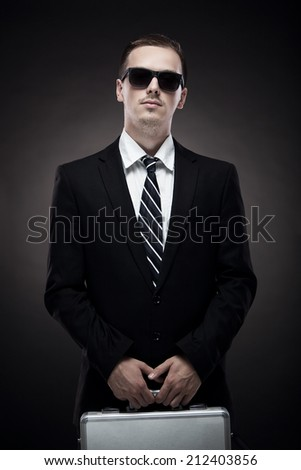 Portrait Of Young Man With  Suitcase On Black Background - stock photo