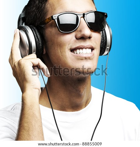 portrait of young man with sunglasses playing to music on a blue background - stock photo