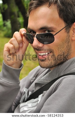 portrait of young man with sunglasses smiling - stock photo