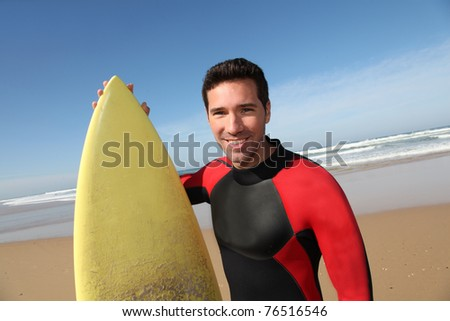 Portrait of young man with surfboard - stock photo