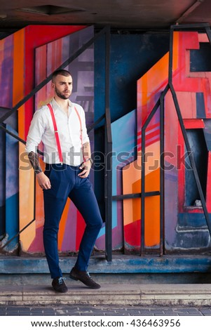 Portrait of young man with tattoos leaning against wall painted with colorful graffiti - stock photo