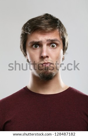 Portrait of young man with thoughtful expression  isolated over background