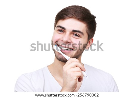 Portrait of young man with toothbrush in hand isolated on white - stock photo