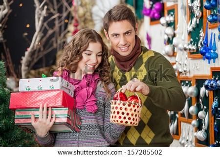 Portrait of young man with woman shopping presents in Christmas store - stock photo