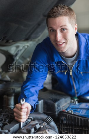 Portrait of young man working on car engine