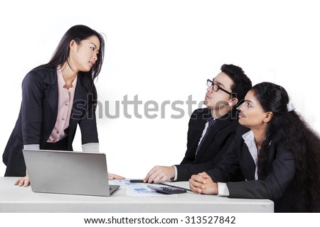 Portrait of young manager having argument with her employees and look angry, isolated on white - stock photo
