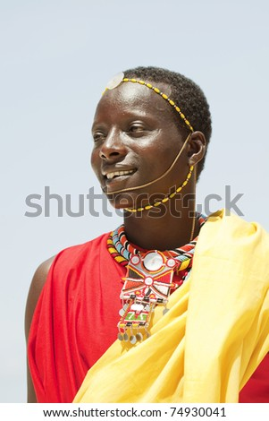 Portrait of young Masai man posing on bright sunny ocean beach; portrait with narrow focus