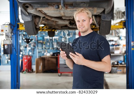 Portrait of young mechanic holding digital tablet in his auto repair shop - stock photo