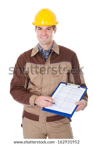 Portrait Of Young Mechanic Wearing Hardhat With Clipboard - stock photo