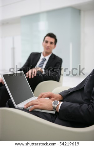 Portrait of young men sitting with a laptop computer - stock photo