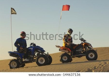 Portrait of young men with helmets sitting on quad bikes in the desert - stock photo