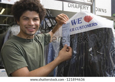 Portrait of young mixed race man holding receipt while standing by clothes rail - stock photo