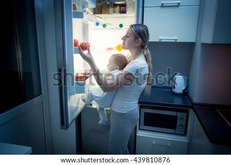 Portrait of young mother and baby son looking inside the fridge for something to eat