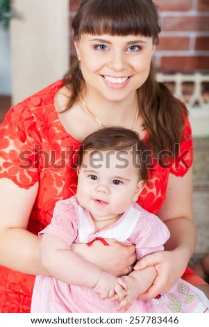 Portrait of young mother and her baby daughter - stock photo