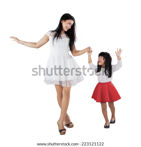 Portrait of young mother and her daughter holding hands in the studio - stock photo