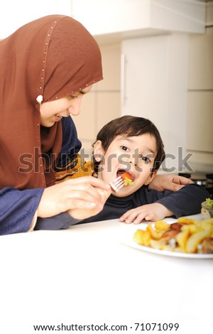 Portrait of young mother and her son having lunch together - stock photo