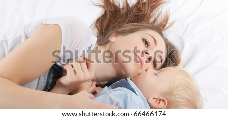 Portrait of young mother and her son lying on the bed.