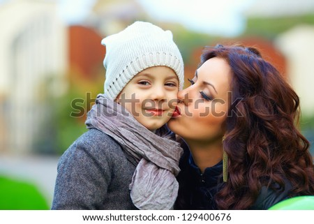 portrait of young mother kissing son outdoors