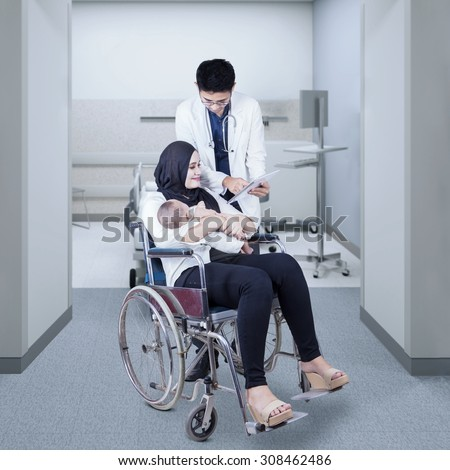 Portrait of young mother sitting on wheelchair with her baby, looking at the checkup result on the tablet with her doctor in hospital