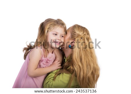 Portrait of young mother whispering secrets to her  adorable daughter 's ear over white background - stock photo