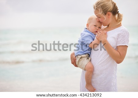 Portrait of young mother with her adorable little boy on the ocean beach. Happy woman hugging a baby and enjoying vacation by the sea. Motherhood, family and lifestyle concept - stock photo