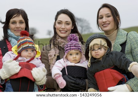 Portrait of young mothers with babies in slings at park - stock photo
