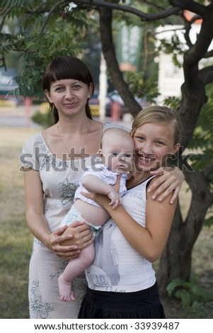 Portrait of young mum with two children - stock photo