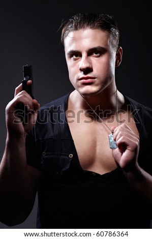 Portrait of young muscular man with gun in his hand - stock photo