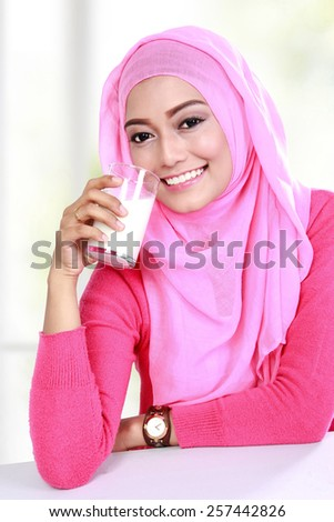 portrait of young muslim woman drinking a glass of milk for breakfast - stock photo
