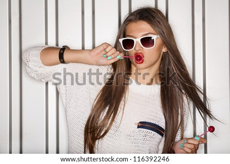 Portrait of young naughty girl sucking lollipops, outdoors - stock photo