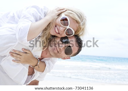 Portrait of young nice couple having good time on the beach - stock photo