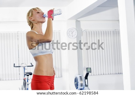 Portrait of young nice woman getting busy in gym