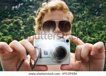 Portrait of young nice woman taking photo in summer environment - stock photo