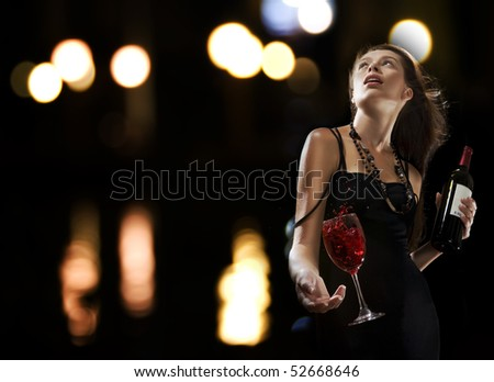 Portrait of young nice woman with glass of wine on black  back - stock photo