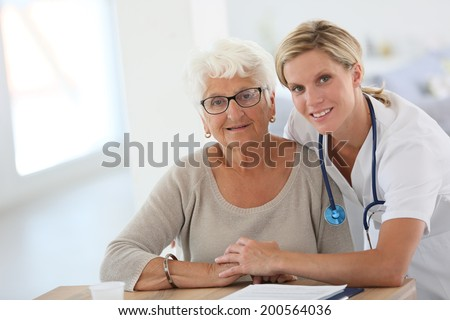 Portrait of young nurse with elderly woman - stock photo